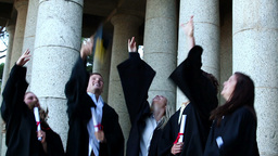 Graduates students throwing mortar boards in the a Stock Video Footage