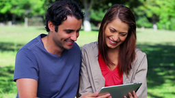 Happy couple holding a tablet computer Stock Video Footage