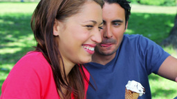 Smiling couple eating ice creams while sitting on  Footage