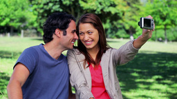 Smiling couple sitting while photographing themsel Footage