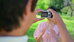 Smiling man photographing his girlfriend Stock Video Footage
