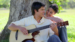 Smiling man playing guitar for his girlfriend Stock Video Footage