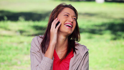 Smiling brunette woman using her mobile phone Footage