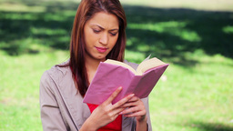 Brunette woman reading an interesting book Footage