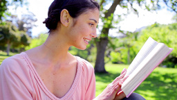 Happy brunette woman reading a novel Footage