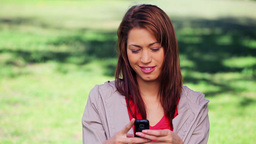 Smiling brunette woman texting on her cellphone Stock Video Footage