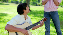 Smiling man playing music with his guitar for his Stock Video Footage