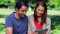 Smiling couple looking at a tablet pc Stock Video Footage
