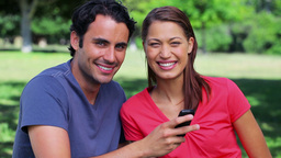 Happy couple looking at a mobile phone Footage