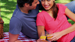 Smiling couple sitting on a blanket during a picni Footage