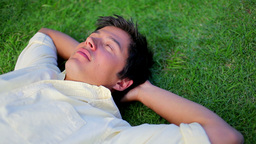 Peaceful man sleeping on the grass Stock Video Footage
