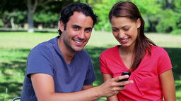 Happy couple looking at a text on a mobile phone Footage