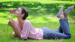 Smiling woman lying on the grass while holding a f Footage