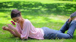 Smiling woman lying on the grass while holding a f Stock Video Footage