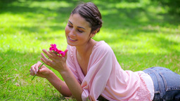 Smiling young woman holding a pink flower Stock Video Footage