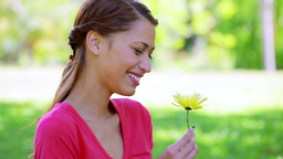 Happy brunette woman holding a yellow flower Stock Video Footage