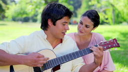 Brunette man playing guitar for his girlfriend Live Action