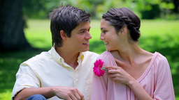 Smiling couple sitting on the grass with a pink fl Footage