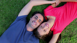 Smiling couple lying on the grass while enjoying the nature Stock Video Footage