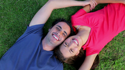 Smiling couple lying on the grass while enjoying t Stock Video Footage