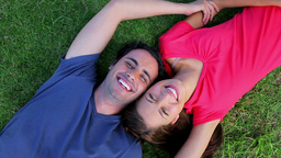 Smiling couple lying on the grass while enjoying t Footage