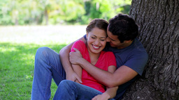 Happy couple leaning against a tree Footage