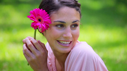 Happy brunette woman holding a pink flower Footage