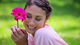 Happy brunette woman holding a pink flower Stock Video Footage