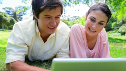 Smiling couple lying on the grass while watching a Stock Video Footage
