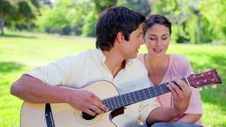 Smiling man singing while playing the guitar Footage