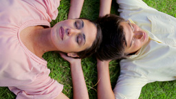 Happy couple lying together on the grass Stock Video Footage