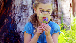 Girl using a magnifying glass Stock Video Footage