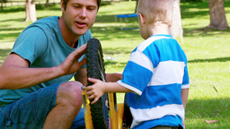 Man playing with a bike wheel with his son Stock Video Footage