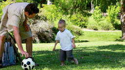 Father playing with his son with a football Footage