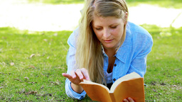 Woman reading while lying on front Stock Video Footage
