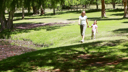 Mother holding her daughters hand while walking Footage