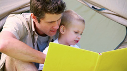 Little boy looking picture book with his father Footage