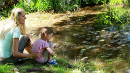 Mother and daughter nourishing a duck Footage
