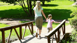 Mother and daughter walking on a bridge Footage