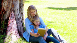 Woman reading a novel with her daughter Footage
