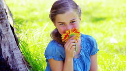 Little girl smelling a flower Footage