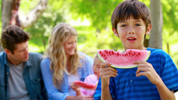 Boy eating watermelon with his family Footage