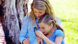 Daughter and mother using a magnifying glass Footage