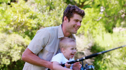 Boy laughing while fishing with his father Footage