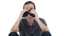 A sitting man is looking through binoculars Stock Video Footage