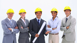 Business team wearing hardhats standing side by side Live Action