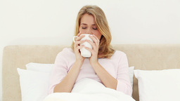 Smiling blonde woman drinking a coffee Stock Video Footage