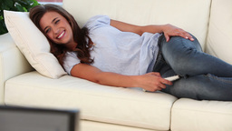 Smiling woman lying while watching the television Footage