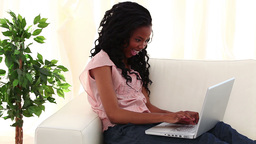Smiling woman typing on a laptop Footage