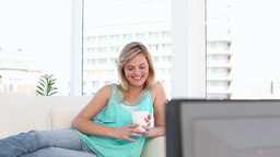 Cheerful blonde woman watching the television Footage
